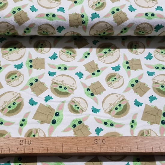 Cotton Flannel Baby Yoda Mandalorian White fabric - Cotton flannel fabric licensed with drawings of the character Baby Yoda (The Child) from the Star Wars The Mandalorian series from the Disney+ platform, on a white background with green frogs. The fabric