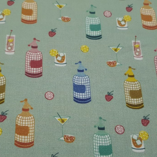Cotton Vermouth Siphons fabric - Organic cotton fabric with drawings of siphons and glasses of aperitif or vermouth drinks on a light green background with small fruits. The fabric is 150cm wide and its composition is 100% cotton.