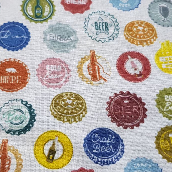 Cotton Beer Badges fabric - Organic cotton fabric with pictures of colorful beer bottle caps on a white background. The fabric is 150cm wide and its composition is 100% cotton.