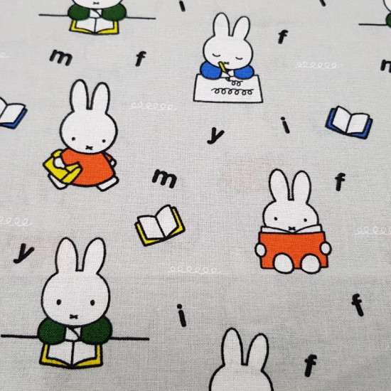 Tela Algodón Miffy Escribiendo - Tela de algodón licencia con dibujos de los personaje Miffy escribiendo y leyendo sobre un fondo de color gris con letras. Esta tela forma parte de la colección Miffy At School de The Craft Cotton Company. La tel