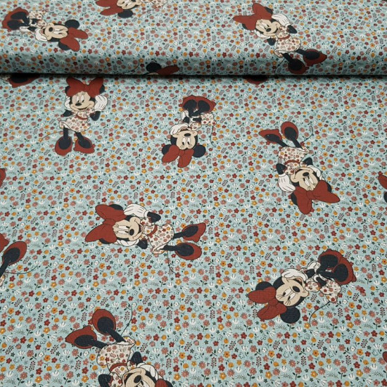 Cotton Disney Minnie Flowers Blue fabric - Children's cotton fabric with drawings of Disney's Minnie character on a flowered background where the light blue color predominates. The fabric is 140cm wide and its composition 100% cotton.