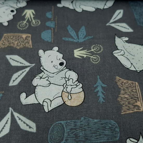 Cotton Disney Winnie Forest Gray fabric - Disney licensed cotton fabric with cute drawings of Winnie the Pooh bear eating a jar of honey and picking up a sheet, in a gray forest with logs and vegetation. The fabric is 110cm wide and its composition is 100