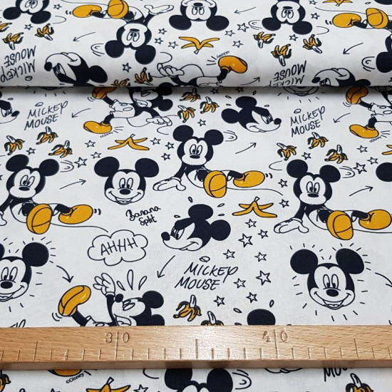 Cotton Disney Mickey Bananas fabric - Disney licensed cotton fabric with drawings showing Mickey slipping on the skin of bananas. The fabric is 150cm wide and its composition is 100% cotton.