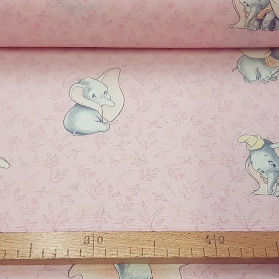 Disney Cotton Dumbo Floral Pink fabric - Disney licensed cotton fabric with drawings of the classic character Dumbo on a flowered pink background. The fabric is 140cm wide and its composition is 100% cotton.