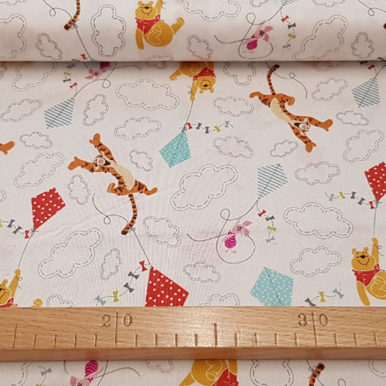 Cotton Disney Winnie Kites fabric - Children's cotton fabric Disney with drawings of Winnie the Pooh, Tigger and Piglet on a white background with colorful kites and clouds.
