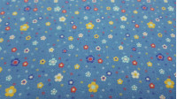Cotton Flowers Daisies Colors Blue Background fabric - Cotton fabric with drawings of flowers and daisies in various colors and sizes on a blue background. The fabric is 150cm wide and its composition is 100% cotton.