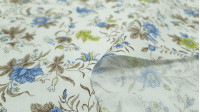 Fine Cotton Flowers Green Blue fabric - Fine batiste cotton fabric with floral patterns in shades of brown, blue and green on a white background. The fabric is 140cm wide and its composition is 100% cotton.