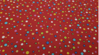 Cotton Multicolor Polka Dots Red Background fabric - Poplin cotton fabric with drawings of multicolored polka dots of different sizes on a red background. The fabric is 150cm wide and its composition is 100% cotton.