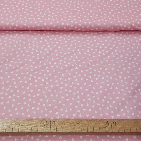 Cotton White and Pink Hearts fabric - Cotton fabric with drawings of small white hearts on a pink background. The fabric is 150cm wide and its composition is 100% cotton.