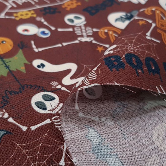 "Cotton Halloween Boo to you fabric - Halloween themed cotton fabric with drawings of dancing skeletons, scarecrows with pumpkin heads, bats and the letters ""Happy Halloween"" and ""Boo to you""... on a maroon-brown background. The fabric is 150cm wide and"