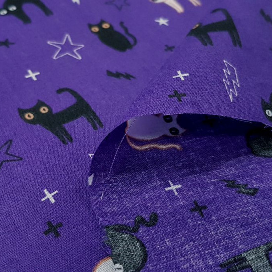 Polycotton Halloween Cats Violet fabric - Fine polyester and cotton fabric with Halloween drawings with black and white cats on a purple background with rays and stars. The fabric is 110cm wide and its composition is 80% polyester - 20% cotton.