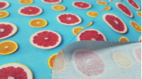 Cotton Grapefruits Oranges fabric - Organic cotton fabric with drawings of grapefruits and oranges cut in half on a turquoise blue background. The fabric is 150cm wide and its composition is 100% cotton.