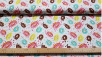 Cotton Donuts Colors fabric - Cotton fabric with drawings of colored glazed donuts on a white background with confetti. The fabric is 150cm wide and its composition is 100% cotton.