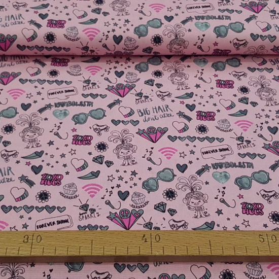 Cotton Trolls Peace Love Pink fabric - Dreamworks licensed children's cotton fabric with drawings of Trolls, with many objects, symbols, phrases... on a pink background. The fabric is 150cm wide and its composition is 100% cotton.