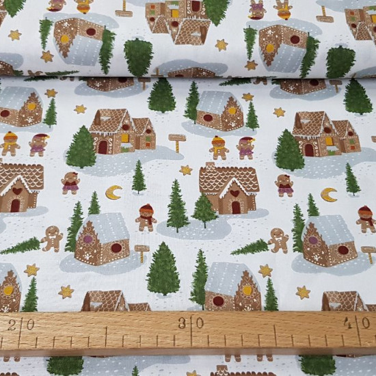 Cotton Christmas Gingerbread Houses fabric - Organic cotton fabric with Christmas drawings where gingerbread houses appear in a forest with snow and fir trees, where there are also funny gingerbread figures. The fabric is 150cm wide and its composition is
