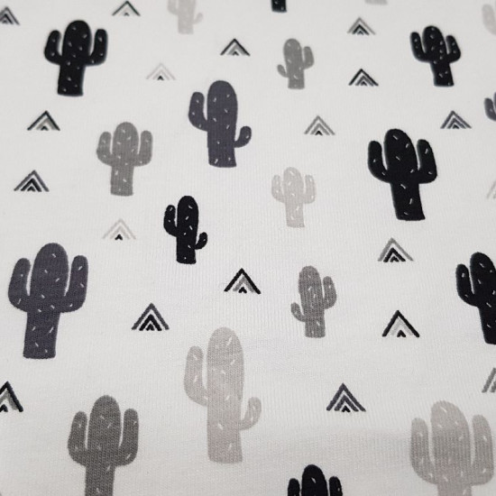 Cotton Jersey Cactus Tipi fabric - Cotton jersey fabric with drawings of cactus and triangles in tipi tents in black and gray colors on a white background. The fabric is 150cm wide and its composition is 95% cotton - 5% elastane