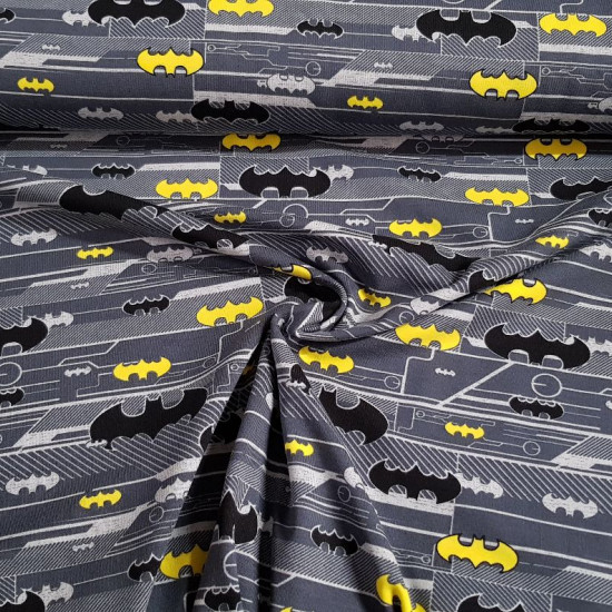 Cotton Jersey Batman Logos fabric - Licensed cotton jersey fabric with drawings of Batman logos in various colors and sizes on a background where gray colors predominate. The fabric is 150cm wide and its composition is 92% aglodon - 8% elastane.