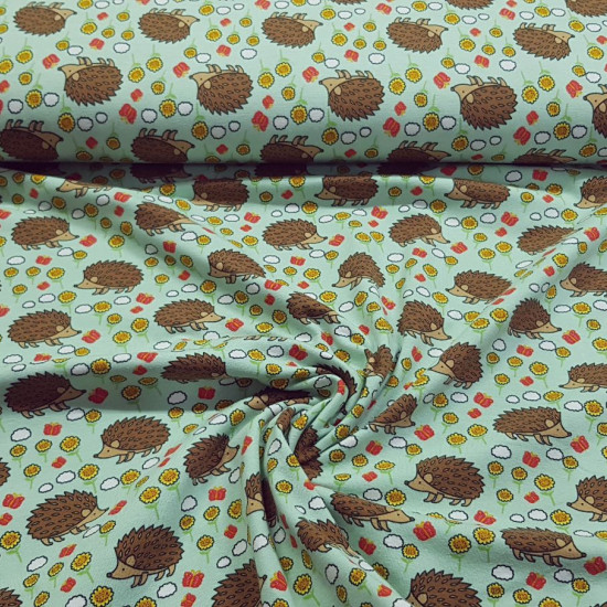 Cotton Jersey Hedgehogs Flowers Green fabric - Cotton jersey fabric with drawings of hedgehogs and flowers on a green background. The fabric is 150cm wide and its composition 95% cotton - 5% elastane