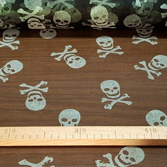 Tulle Skulls fabric - Semi-transparent tulle fabric with drawings of bright pirate skulls on black grid background. A prefect fabric for Halloween and carnival costumes. The fabric measures 150cm and its composition 80% polyester - 20% gl