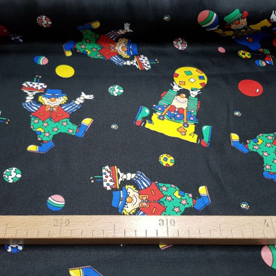 Satin Clowns Black Background fabric - Satin fabric with drawings of colored clowns on a black background. The satin fabric has shine on one side and has quite a drop. The fabric is 150cm wide and its composition 100% polyester.