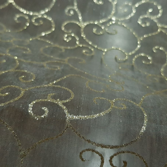 Organza Golden Tangled fabric - Semi-transparent organza fabric in gold color with tangles and shiny shapes in gold color. The fabric is 150cm wide and its composition 100% polyester