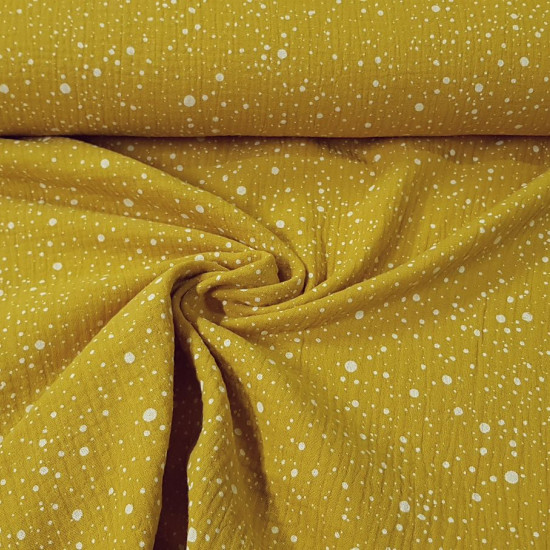 Double Gauze Splash Ocher fabric - Double gauze or muslin fabric with white splatter patterns in various sizes on an ocher background. The fabric is 130cm wide and its composition is 100% cotton.