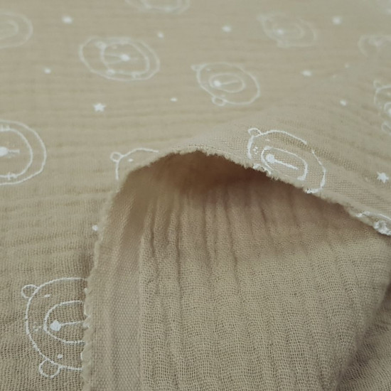Double Gauze Bears Stars fabric - Double gauze or muslin fabric for children with drawings of faces of bears and stars on a sandy background. The fabric is 135cm wide and its composition is 100% cotton.
