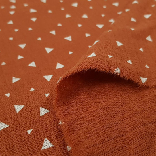 Double Gauze Triangles fabric - Double gauze or muslin fabric with white triangle patterns on a terracotta background. The fabric is 130cm wide and its composition is 100% cotton.