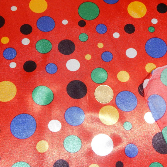 Satin Topos Multicolor Red Background fabric - Satin fabric, bright on one side and with a lot of fall. Polka dot print in various colors on red background. Ideal for clown costume. The fabric is 150cm wide and its composition 100% polyester.